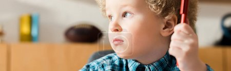 panoramiczne ujęcie uroczego dziecka odwracającego wzrok i trzymającego długopis