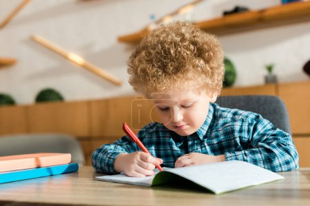 smart child writing in notebook near books on table