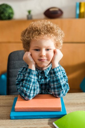 smart child looking at camera near books on table