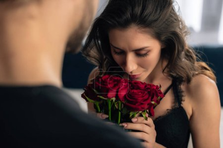 Photo for Cropped view of attractive girlfriend smelling roses from boyfriend in 14 february - Royalty Free Image