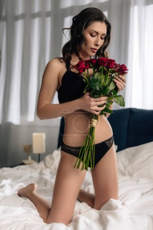 attractive woman in lace bra and panties holding bouquet