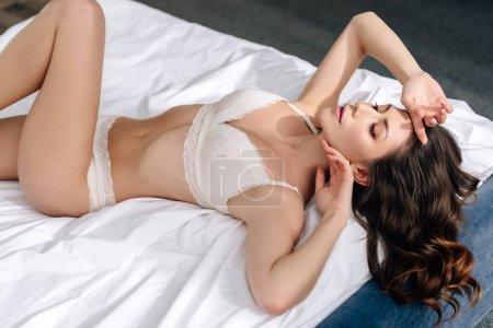 Hochwinkelaufnahme der attraktiven Frau in BH und Höschen auf dem Bett liegend