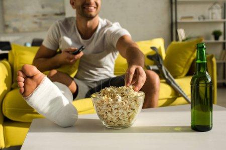 Photo pour Vue croustillante d'un homme souriant dont la jambe cassée prend du maïs soufflé près d'une bouteille de bière regardant la télévision à la maison - image libre de droit