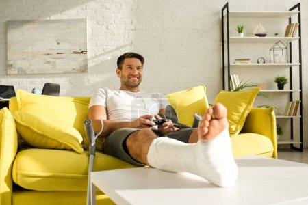 Photo pour Kyiv, Ukraine - 21 janvier 2020 : Handsome smiling man with broken leg on coffee table playing video game in living room - image libre de droit