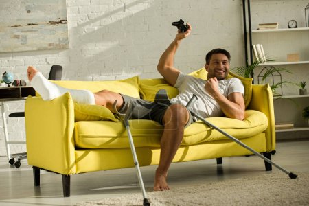 KYIV, UKRAINE - JANUARY 21, 2020: Exited man with broken leg holding joystick and showing win gesture on couch at home