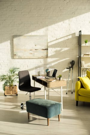Photo for Living room with laptop on table and crutches near wall - Royalty Free Image