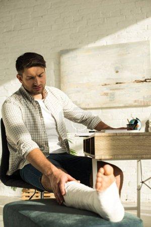 Photo pour Foyer sélectif de bel homme touchant jambe cassée tout en étant assis à la table dans le salon - image libre de droit