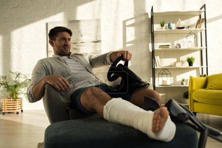 Photo pour Bel homme avec jambe cassée jouer jeu vidéo avec volant dans le salon - image libre de droit