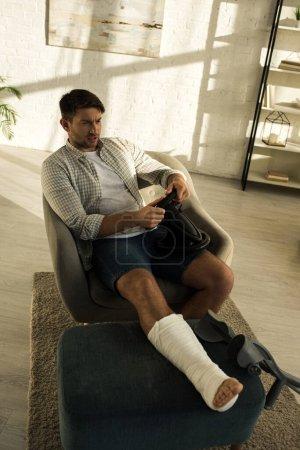 Photo pour Vue à grand angle d'un homme avec jambe cassée sur un ottoman jouant à un jeu vidéo avec volant à la maison - image libre de droit
