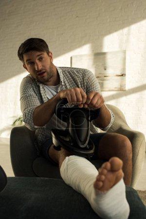 Photo pour Focus sélectif de l'homme avec jambe dans un pansement de plâtre tenant le volant dans le salon - image libre de droit