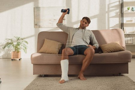 Man with broken leg sitting on couch and training with dumbbells at home