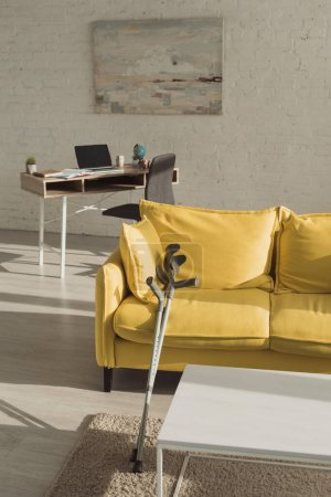 Photo for Sunlit living room with crutches near yellow sofa - Royalty Free Image
