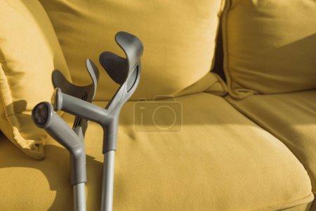 Photo pour Béquilles près du canapé jaune avec lumière du soleil - image libre de droit