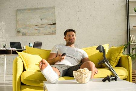 Photo pour Kyiv, Ukraine - 21 janvier 2020 : Selective focus of smiling man with broken leg watching tv near popcorn and joystick on coffee table - image libre de droit