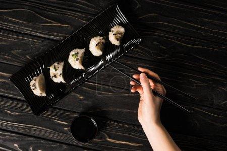 Photo pour Vue partielle d'une femme en train de manger un délicieux dumpling chinois bouilli avec des baguettes et de la sauce de soja à table noire en bois - image libre de droit