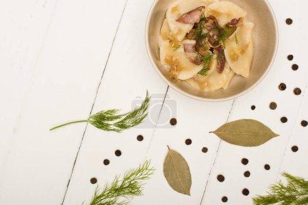 Photo pour Vue de dessus de délicieux varenyky avec des craquelins et de l'aneth dans un bol près des feuilles de laurier et des grains de poivre noir sur une table en bois blanc - image libre de droit