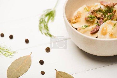 Photo pour Foyer sélectif de délicieux varenyky avec des craquelins et de l'aneth dans un bol près des feuilles de laurier et des grains de poivre noir sur une table en bois blanc - image libre de droit
