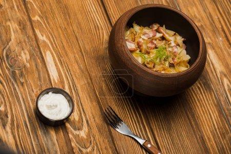 Photo pour Délicieux varenyky avec craquelins dans un bol servi avec crème sure sur une table en bois - image libre de droit