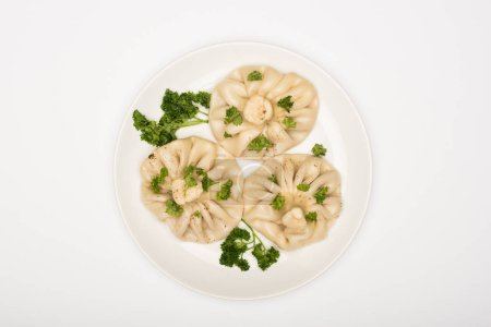 Photo for Top view of delicious Khinkali with cilantro on plate on white background - Royalty Free Image