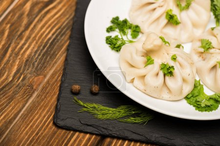 Photo for Close up view of delicious Khinkali with cilantro on plate on brown wooden table - Royalty Free Image