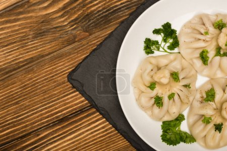 Photo for Top view of delicious Khinkali with cilantro on plate on brown wooden table - Royalty Free Image