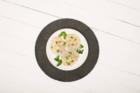 Photo for Top view of delicious Khinkali with cilantro on plate on white wooden table - Royalty Free Image