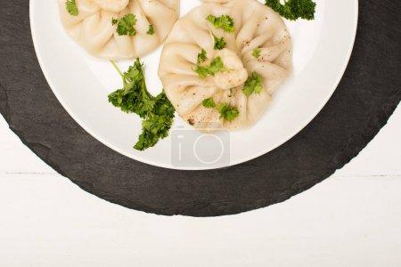 Photo pour Top vue de délicieux Khinkali avec coriandre sur plaque sur table blanche en bois - image libre de droit