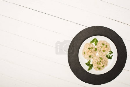 top view of delicious Khinkali with cilantro on plate on white wooden table