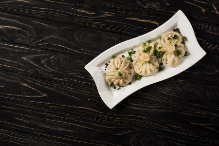 Photo pour Vue de dessus de délicieux Khinkali avec coriandre sur plaque sur table en bois noir - image libre de droit