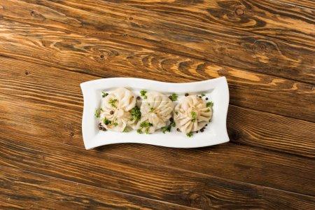 Photo pour Vue de dessus de délicieux Khinkali avec coriandre sur plaque sur table en bois marron - image libre de droit