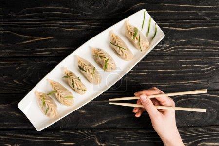 Photo pour Vue en coupe d'une femme qui mange un délicieux dumpling chinois bouilli avec des baguettes à table noire en bois - image libre de droit