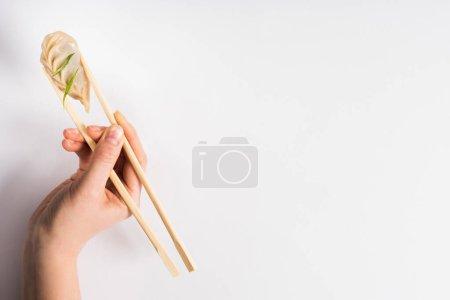 Photo pour Crochet représentant une femme tenant un délicieux dumpling chinois bouilli avec des baguettes sur fond blanc - image libre de droit