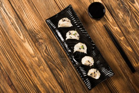 Photo for Top view of delicious Chinese boiled dumplings on plate near chopsticks and soy sauce on wooden table - Royalty Free Image