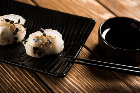Photo for Close up view of delicious Chinese boiled dumplings on plate near chopsticks and soy sauce on wooden table - Royalty Free Image