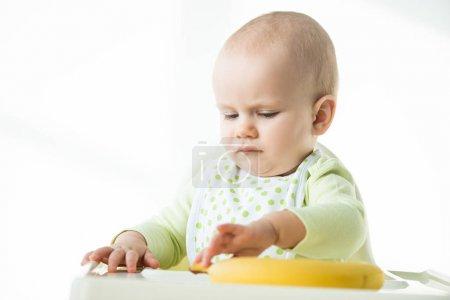 Photo pour Concentration sélective du bébé assis sur la chaise d'alimentation avec banane sur la table sur fond blanc - image libre de droit
