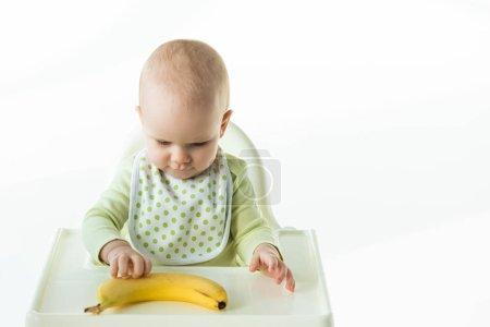 Photo pour Bébé toucher banane mûre tout en étant assis sur la chaise d'alimentation sur fond blanc - image libre de droit