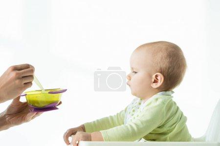 Photo pour Vue latérale de la mère tenant bol de nutrition pour bébé et cuillère près du nourrisson sur chaise d'alimentation sur fond blanc - image libre de droit