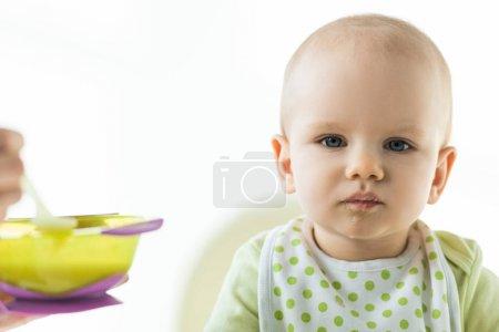 Photo pour Focus sélectif du nourrisson sur la chaise d'alimentation regarder la caméra près de la mère avec bol de purée isolé sur le blanc - image libre de droit
