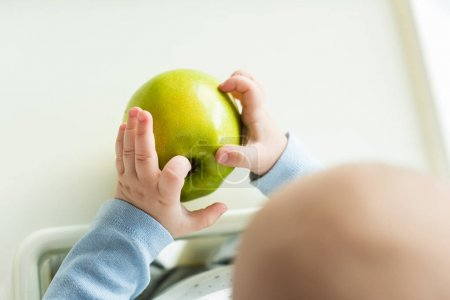 Photo for Overhead view of baby holding green apple while sitting on feeding chair - Royalty Free Image