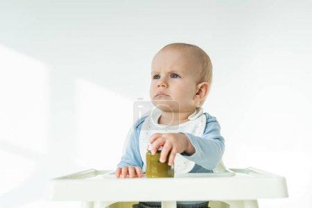 Photo pour Bébé garçon mignon tenant pot de purée de légumes et regardant loin sur la chaise d'alimentation sur fond blanc - image libre de droit