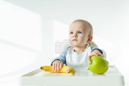 Photo for Adorable baby holding ripe banana and apple on table of feeding chair on white background - Royalty Free Image