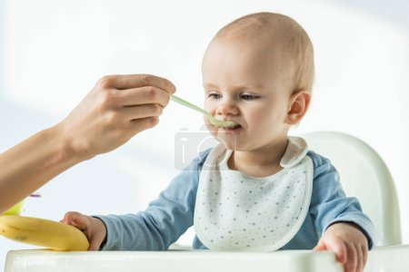 Photo for Mother feeding baby son while holding banana on table of feeding chair on white background - Royalty Free Image