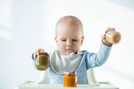 Photo pour Concentration sélective des pots de maintien de bébé de légumes nutrition bébé tout en étant assis sur la chaise d'alimentation sur fond blanc - image libre de droit