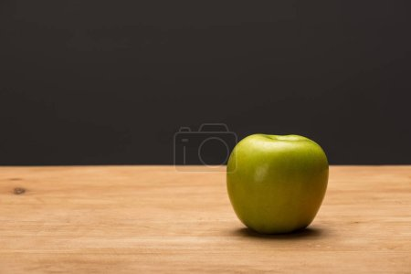 Photo for Green apple on wooden surface isolated on black - Royalty Free Image