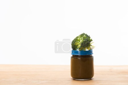 Photo for Jar of vegetable baby food with piece of broccoli on wooden surface isolated on white - Royalty Free Image
