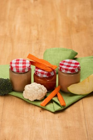 Photo for Jars of baby food with cauliflower, broccoli and carrot on napkin on wooden surface - Royalty Free Image