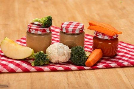 Photo pour Pots de légumes nutrition bébé avec des légumes frais et pomme sur la serviette sur la surface en bois - image libre de droit