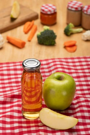 Photo for Selective focus of bottle with apple juice and jars of baby food with ingredients on tablecloth on wooden surface - Royalty Free Image