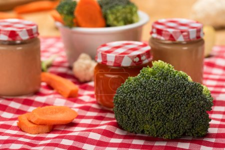 Photo for Close up view of fresh broccoli, carrot and cauliflower with jars of baby food on tablecloth on wooden surface - Royalty Free Image