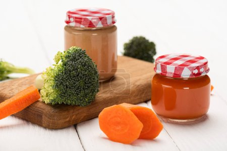Photo for Close up view of fresh broccoli, carrot and jars of baby food on cutting board on white wooden background - Royalty Free Image